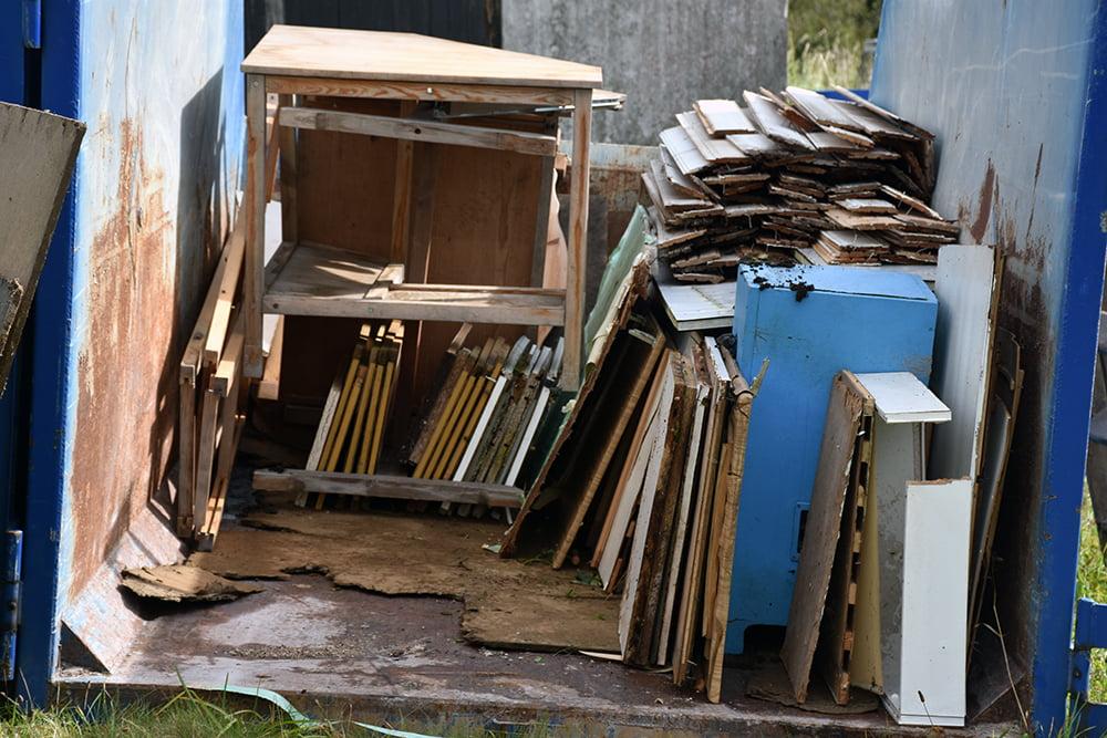 Containern med trä - spånplattor, köksluckor, halvruttna plankor, bräder med plastfärg.